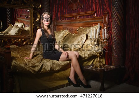 Fashion photo of sexy brunet woman wearing black dress and mask at bedroom