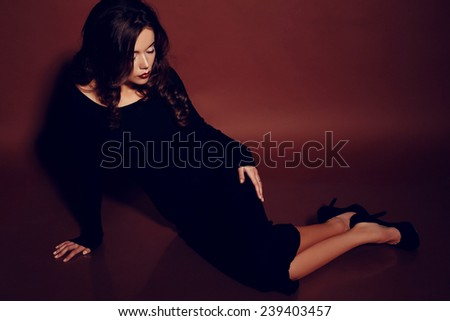 fashion photo of sexy brunette woman in black dress and heeled shoes with red lips and curly hair posing in studio