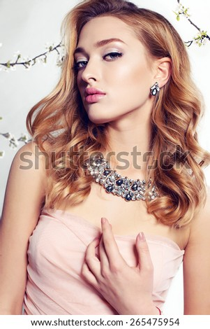 Fashion photo of sexy girl with curly hair wearing a dress,beautiful earrings and necklace,posing at sunny garden around flowering trees - stock photo