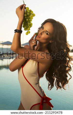 fashion photo of sexy glamour woman with dark curly hair in swimsuit posing beside a swimming pool with bunch of grapes - stock photo