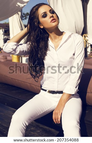fashion photo of sexy glamour woman with long dark wet hair in white shirt and pants sitting on beach - stock photo