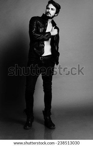 Fashion photo of sexy stylish and  handsome brunette man dressed in a black leather jacket jeans and shoes posing in studio