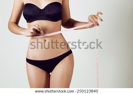 Fashion photo of sexy young woman in lingerie with slim body sitting on a diet and measuring the waist with a centimeter tape - stock photo