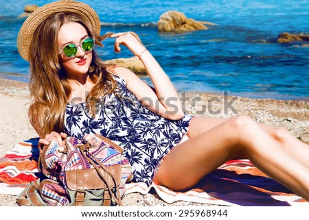 fashion photo of trendy beautiful girl with blond hair in black bikini relaxing beside the sea background,fashion,teen,cool accessories,hat, sunglasses,amazed,vintage style,wall background,hair,wind  - stock photo