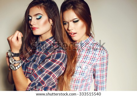 fashion photo of two beautiful young women with long dark hair and bright makeup wears casual clothes,posing in studio