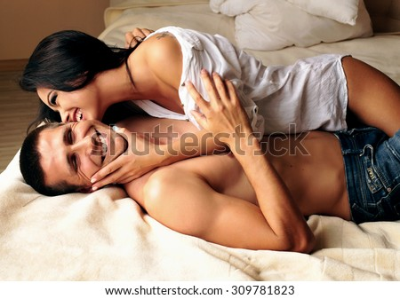 Fashion photo of two young beautiful brunet lovers relaxing and smiling at the hotel on a bed