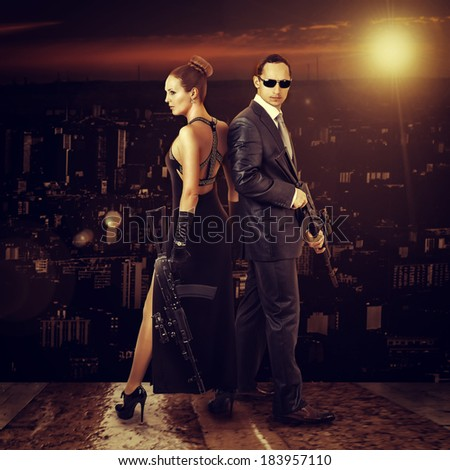 Fashion photo of young beautiful couple - man and woman snipers holding automatics outdoor - stock photo