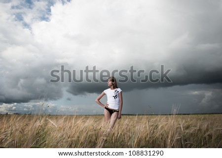 Fashion photo of young beautiful woman standing on a field of wheat against a background of sky and clouds