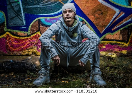 Fashion photo of young guy posing on bright wall - stock photo