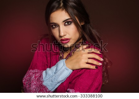 Fashion photo of young magnificent woman in colorful cardigan and jewelry. Posing in studio