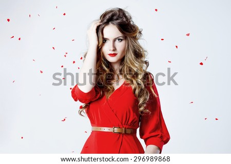 Fashion photo of young magnificent woman in red dress amid rose petals    - stock photo