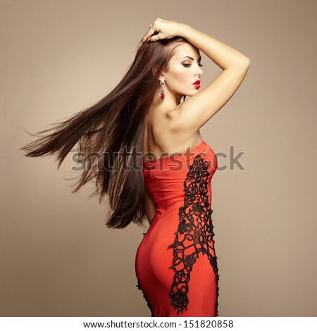 Fashion photo of young magnificent woman in red dress. Studio photo - stock photo