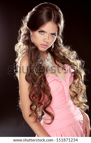 Fashion photo of young magnificent woman. Sexy Girl posing in pink dress with long curly hair isolated on black background. Studio - stock photo