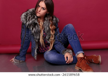 Fashion photo of young sexy girl with long braids hair and bright make-up wearing in plaid shirts,blue jeans and jacket with fur,relaxing and posing at studio - stock photo