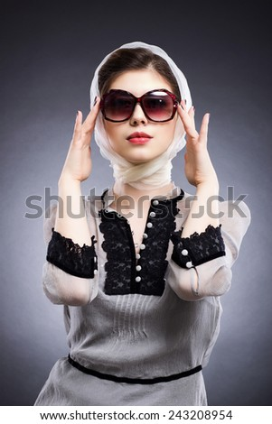 Fashion photo. Portrait of a beautiful woman wearing sunglasses in a retro style.