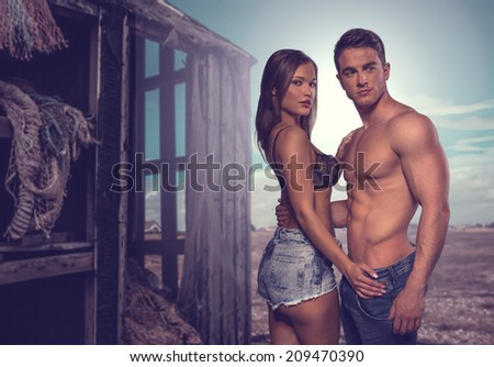 Fashion Photo Shoot. Two Sexy Couple Posing Flaunting Perfect Body Beside Old Wooden House - stock photo