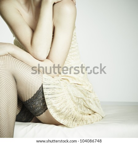 Fashion photo young sexual woman sitting on a sofa. Woman in stockings - stock photo