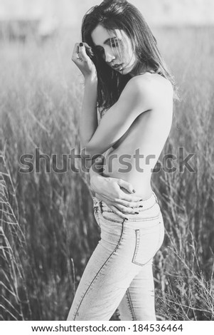 Fashion photograph of young sensual woman in jeans, in nature - stock photo