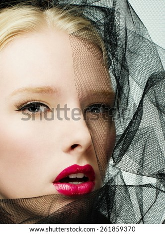 Fashion photography of a beautiful blonde model with black veil - stock photo