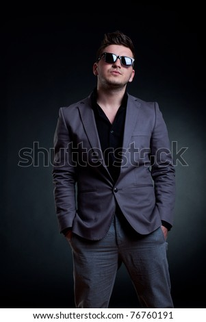 fashion picture of a man with sunglasses standing on a dark background - stock photo