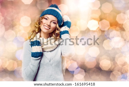 fashion picture of beautiful smiling blonde woman wearing a blue woolen sweater, a scarf and knitted cap  - stock photo