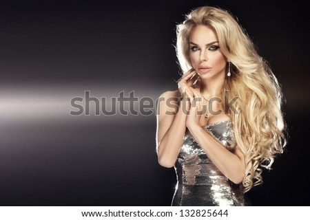 Fashion picture of beautiful young blonde woman wearing glitter silver dress. Long healthy curly hair. - stock photo