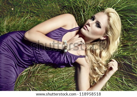 fashion picture of romantic blonde girl lying on grass meadow - stock photo