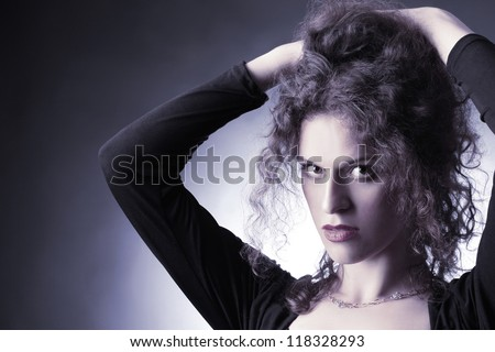 Fashion portrait curly hair woman with hands on the head. Wavy hairstyle