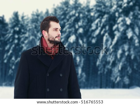 Fashion portrait handsome elegant bearded man wearing black coat in winter day over snowy trees forest background, empty copy space