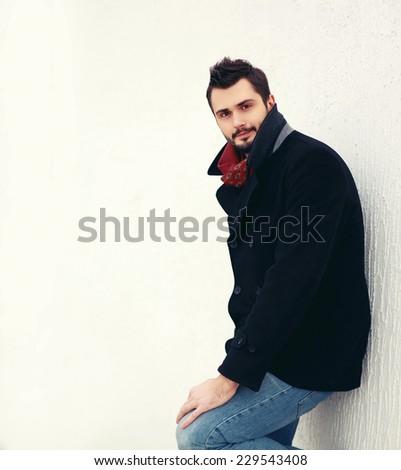 Fashion portrait handsome elegant man in black coat with stylish hairstyle posing on white urban wall background - stock photo