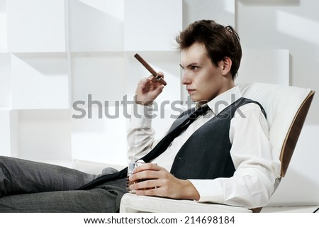 Fashion portrait in modern white office interior. Young handsome man sitting in armchair with cigar and glass of whiskey - stock photo