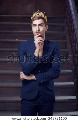fashion portrait male model in suit and crown in ancient interior - stock photo