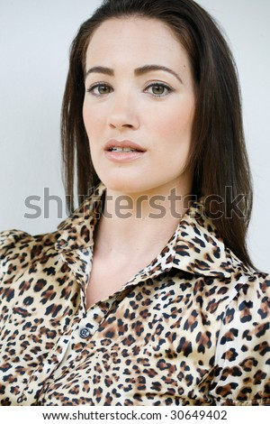 Fashion portrait of a beautiful brunette woman in a leopard print shirt.
