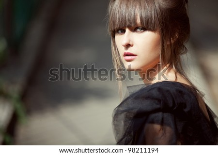 fashion portrait of a beautiful brunette woman on the street - stock photo