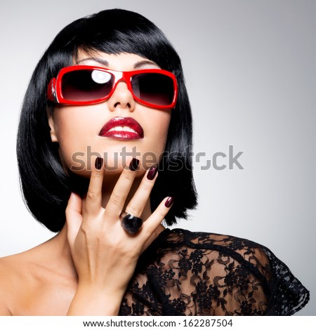 Fashion portrait of a  beautiful brunette woman with shot hairstyle with beauty nails - studio photo