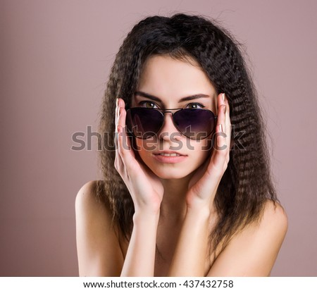 Fashion portrait of a beautiful brunette woman with shot hairstyle with red sunglasses - studio photo