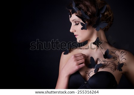 fashion portrait of a beautiful girl in profile on a black background with black butterflies on the body - stock photo