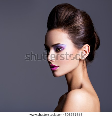 Fashion portrait of a beautiful  girl with creative hairstyle and make-up - at studio