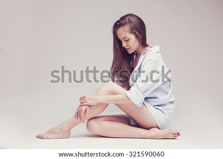 fashion portrait of a beautiful sexy woman with long hair in white shirt sitting on light grey background