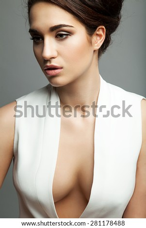 Fashion portrait of a beautiful woman in a dress with a plunging neckline - stock photo