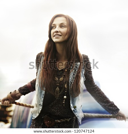 fashion portrait of a beautiful young girl at an amusement park - stock photo