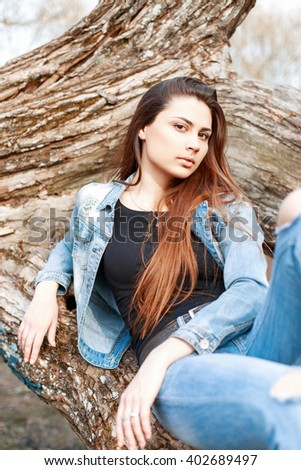 Fashion portrait of a beautiful young girl in denim dress on a background of a tree