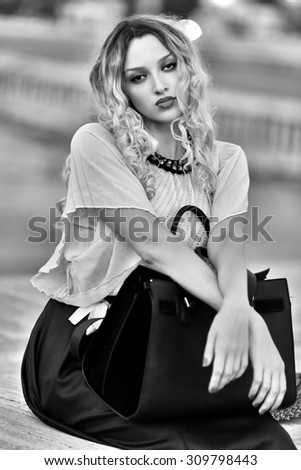 Fashion portrait of a beautiful young sexy woman outdoor. Photo has an INTERNATIONAL FILM GRAIN.