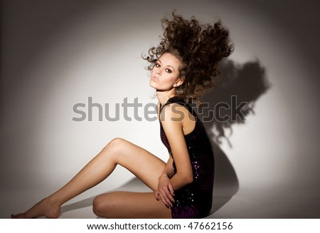 Fashion Portrait of a beautiful young sexy woman posing on gray background