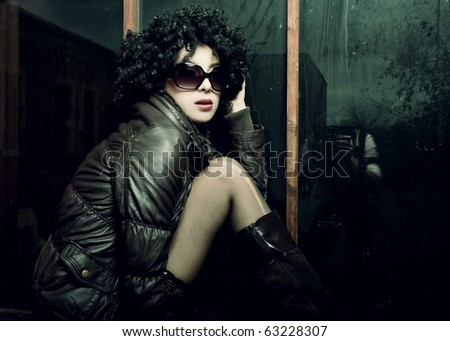 Fashion portrait of a beautiful young sexy woman wearing sunglasses. Art disco style