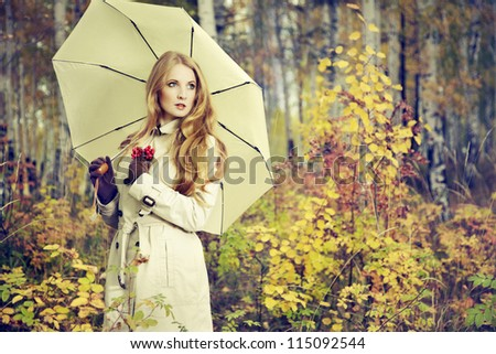 Fashion portrait of a beautiful young woman in autumn forest. Girl with umbrella - stock photo