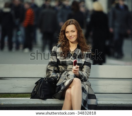 fashion portrait of a beautiful young woman with a mobile phone