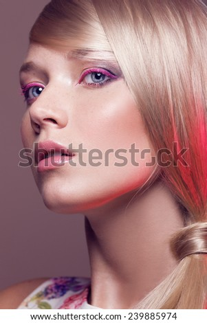 fashion portrait of a blond girl with pink light on the hair - stock photo