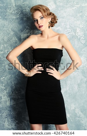 Fashion portrait of a charming young woman in black dress with evening make-up and hairstyle. Beauty, fashion.