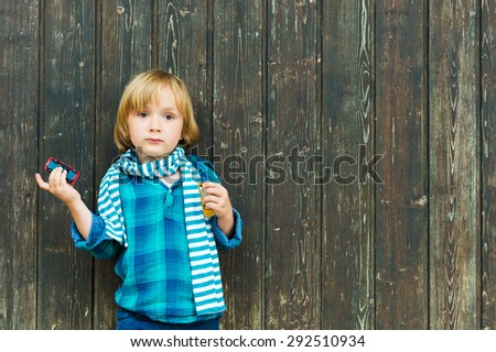 Fashion portrait of a cute little blond  boy against wooden background, wearing emerald shirt and scarf, holding a toy car - stock photo